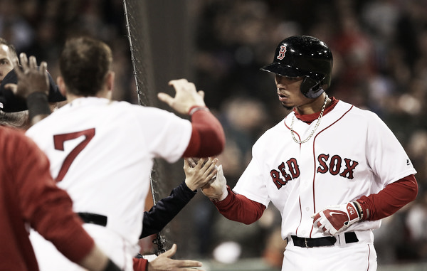 Mookie Betts gets greeted in the Red Sox dugout after scoring in the fourth inning. (Photo:Adam Glanzman/Getty Images North America