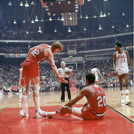 Bill Walton ayudando a Maurice Lucas a levantarse | Foto: Getty Images