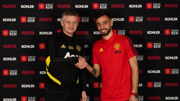 Bruno Fernandes shakes Ole Gunnar Solskjaer's hand as he signs (Photo from Manchester United website)