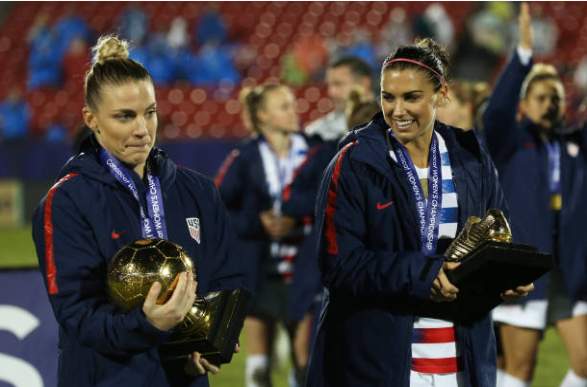 Julie Ertz (left) and Alex Morgan (right) carry their hardware after the USWNT won the 2018 CONCACAF Women's Championship. | Photo: Omar Vega - Getty Images