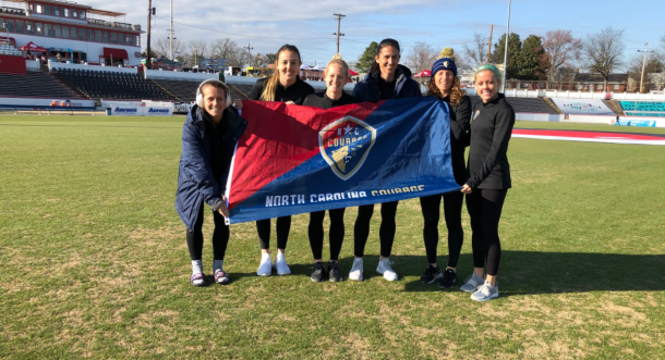 Five Courage players pose with a flag before their preseason game at City Stadium against the Washington Spirit. | Photo: @TheNCCourage
