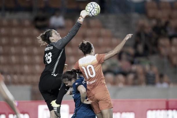 Reign goalkeeper Haley Kopmeyer pushing the ball from midfielder Carli Lloyd. Photo: Seattle Reign