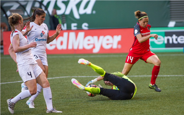 Goalkeeper Nicole Barnhart dives on the ball as Becky Sauerbrunn (far left) hustles back on defense. | Photo: Diego Diaz - Icon Sportswire via Getty Images