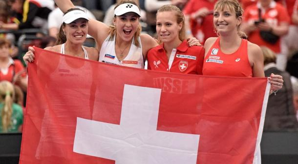 Hingis, Bencic, Golubic and Timea Bacsinszky pose with the Swiss flag after a Fed Cup quarterfinal win over Germany/Jens Meyer/Assoicated Press