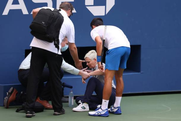 US Open medical personnel tend to the line judge who was struck by a ball hit by Djokovic, who looks on in concern/Photo: Al Bello/Getty Images