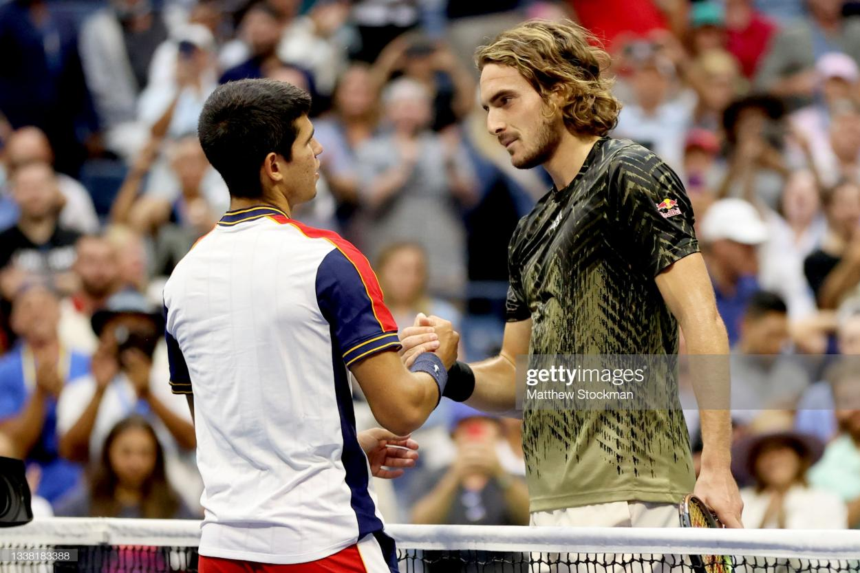 Tsitsipas and Alcaraz share a moment at the net after their match (Matthew Stockman/Getty Images)