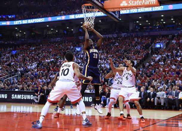 Ian Mahinmi (28) goes up for a putback in between three Raptors (NBAE/Getty Images)