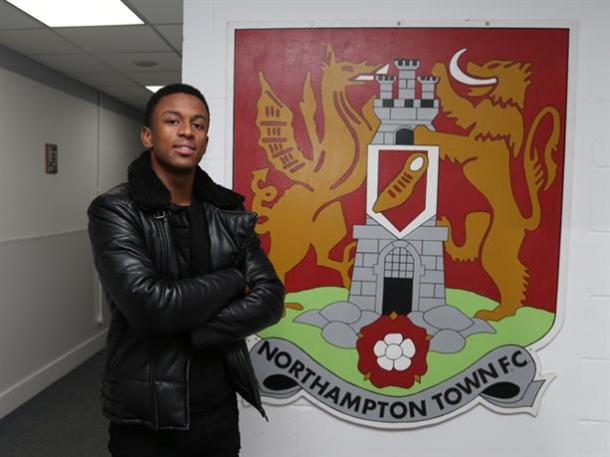 Hanley poses next to the crest that he will wear on his new shirt. (Photo: Northampton Town FC)