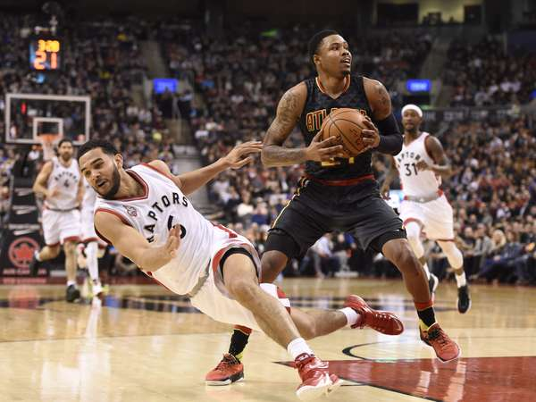 Raptors' Cory Joseph falls as Hawks' Kent Bazemore looks to make a shot. | Frank Gunn/The Canadian Press via AP