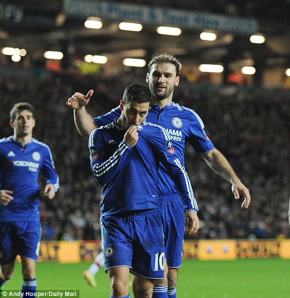Hazard celebrates his first goal of the season by kissing the Chelsea badge