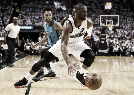 Miami Heat Guard Dwyane Wade passes by Charlotte Hornets Guard Courtney Lee. Steve Mitchell-USA TODAY Sports