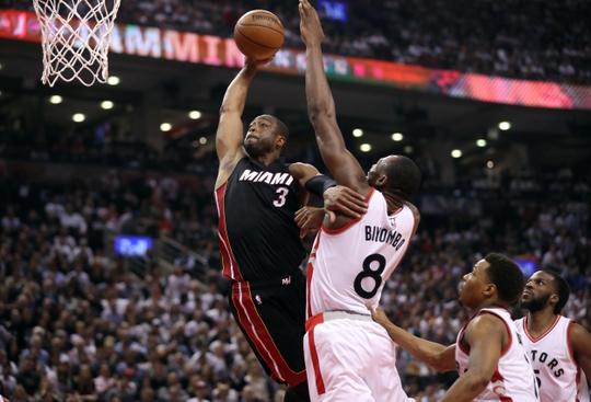 Miami Heat Guard Dwayne Wade attacks the basket before getting blocked by Toronto Raptors center Bismack Biyombo. Photo Credit:Tom Szczerbowski-USA TODAY Sports