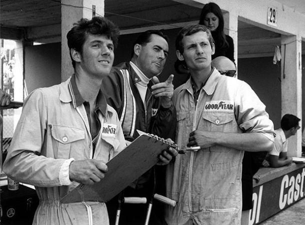 Dennis (R) started life as a mechanic, seen alongside Triple World Champion, Sir Jack Brabham (C) (Image Credit (Pinterest - unknown user)