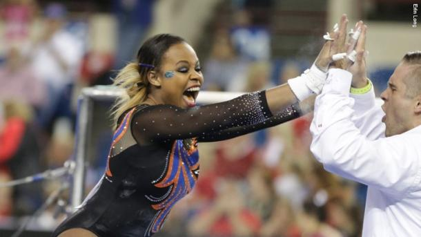 Kennedy Baker celebrates a stuck bar routine with Florida bars coach Adrian Burde at the NCAA Women's Gymnastics Championships/Erin Long