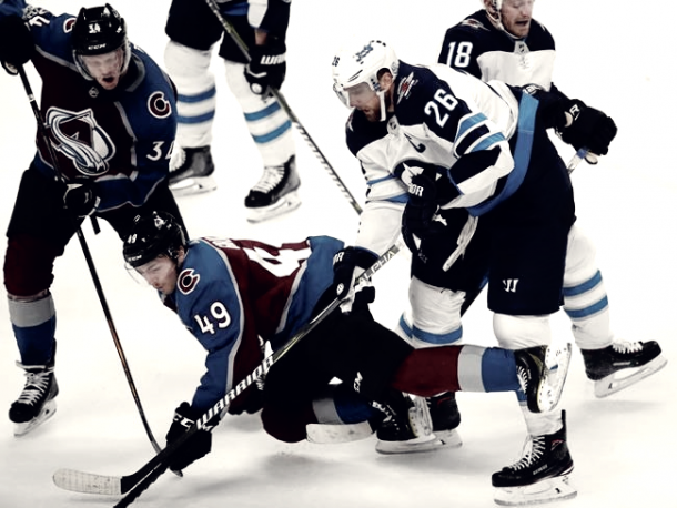 Sam Girard (49) of the Avalanche tried to force his way through the Jet's defense. (AP Photo/David Zalubowski