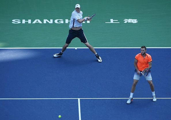John Isner striking a ball with Jack Sock looking on (Photo: Wang Zhao/Getty Image)