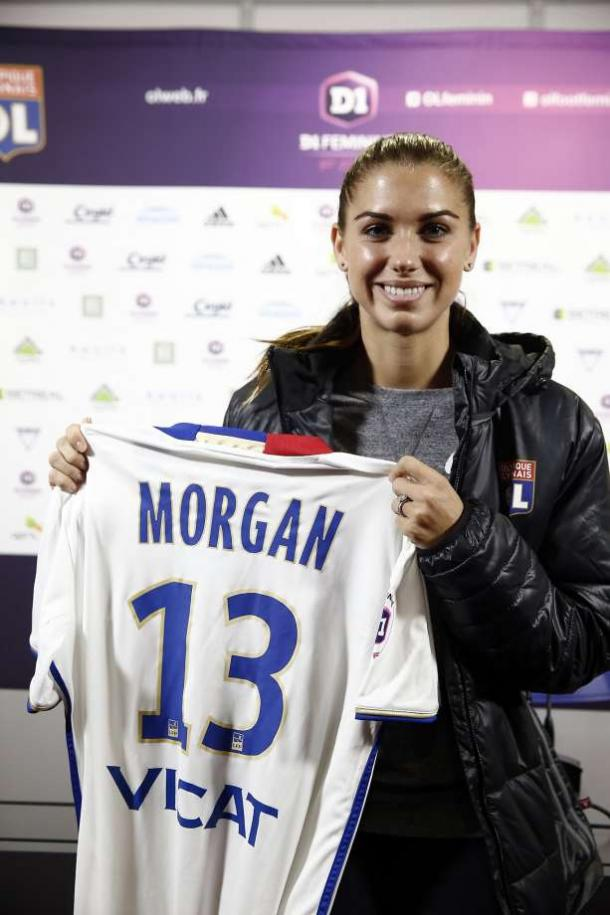Alex Morgan holding her Lyon jersey (Photo: Associated Press)