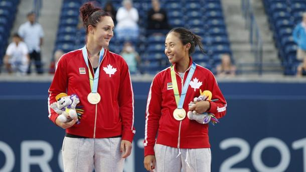 Gabriela Dabrowski and Carol Zhao wait on the podium after receiving their gold medals after winning the women's doubles competition at the Toronto 2015 Pan American Games. | Photo via the Canadian Olympic Committee
