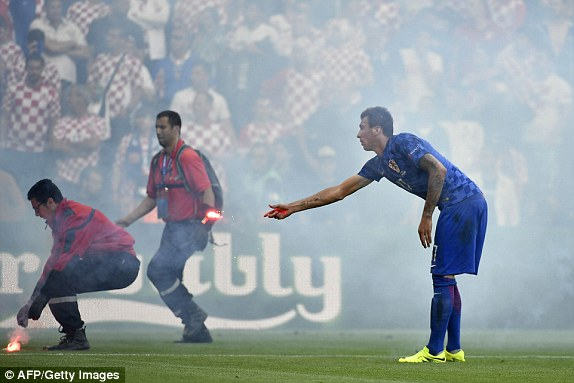 Mario Mandzukic throws a flare off the pitch (photo; Getty Images)