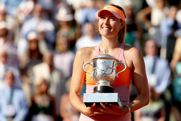 Sharapova posing with her last Grand Slam singles title at the French Open in 2014 (Photo by Matthew Stockman / Getty Images)