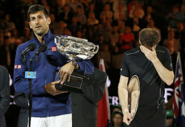 Novak holds the trophy aloft whilst Andy looks understandably downbeat after another Australian Open final loss | Photo: indianexpress.com