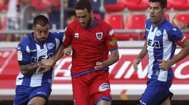 Un jugador del Numancia intenta salir entre dos contrarios del equipo del Deportivo Alavés. Fuente: Wifredo García