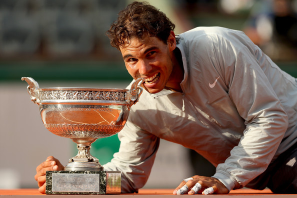 Nadal posing with his most recent Grand Slam singles title at the French Open in 2014 (Photo by Matthew Stockman / Getty Images)