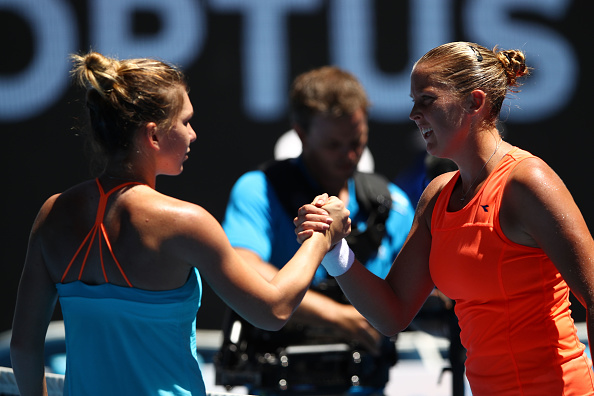 Halep and Rogers shake hands at the net (Photo by Clive Brunskill / Getty Images)