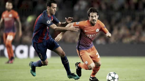 Silva protege el balón ante Busquets. Foto: Manchester City