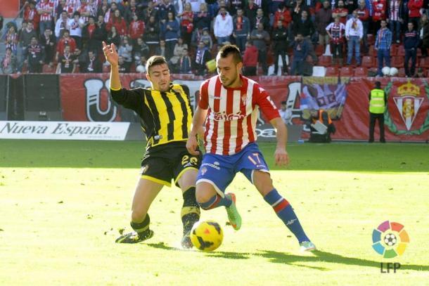 Santi Jara conduce un balón ante la presión de un jugador zaragocista | Imagen: LaLiga