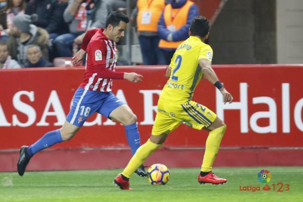 Isma López conduce un balón ante un jugador del Cádiz en El Molinón | Imagen: LaLiga