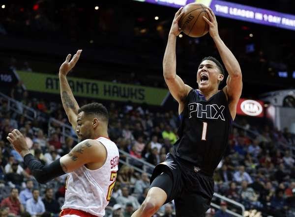 Phoenix Suns' Devin Booker rises above Atlanta Hawks' Thabo Sefolosha to put up points in the first half. | AP Photo: John Bazemore