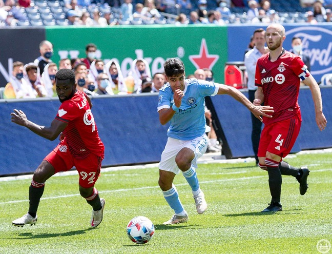 NYCFC midfielder Andres Jasson (c.) plays the ball between Toronto's Kemar Lawrence (l.) and Michael Bradley (r.)/Photo: The NYCFC Nation