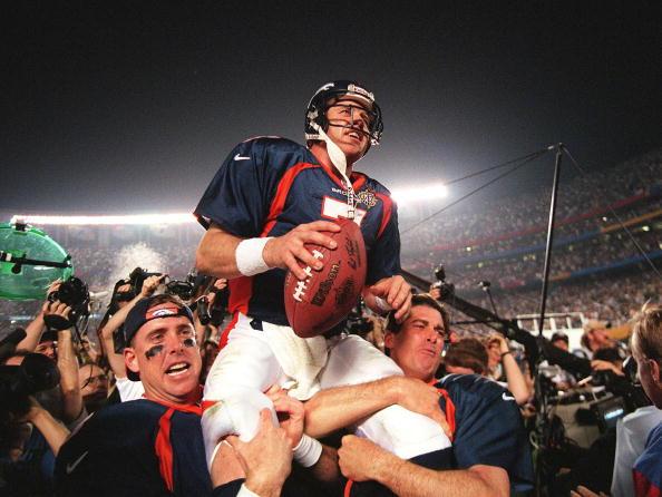 Elway carregado por seus companheiros após o título do Super Bowl XXXII | Foto: Timothy A. Clary/AFP via Getty