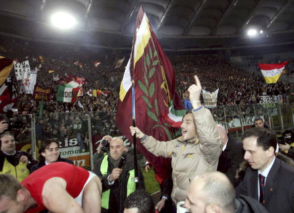 Comemorar vitória sobre o maior rival, do lado da torcida, com um bandeirão na mão? Totti assinou o atestado de torcedor em 2006 (Foto: New Press / Getty Images)