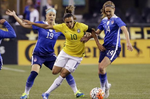USWNT teammates Julie Ertz (left) and Morgan Brian (right) going up against Brazilian, Marta (middle )in 2015. l Photo: Elaine Thompson/AP