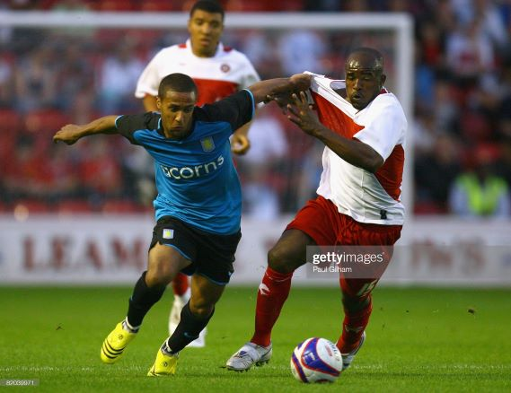 WALSALL, UNITED KINGDOM - JULY 22: Wayne Routledge of Aston Villa battles for the ball with Patrick Suffo of Walsall during the Pre Season Friendly match between Walsall and Aston Villa at the Bescot Stadium on July 22, 2008 in Walsall, England. (Photo by Paul Gilham/Getty Images)