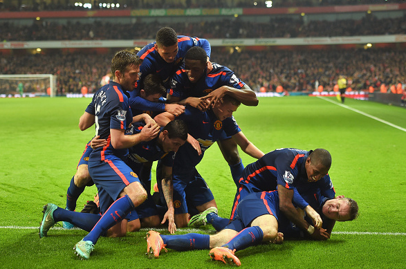 Rooney celebrates his winner alongside his teammates at the Emirates | Photo: Getty