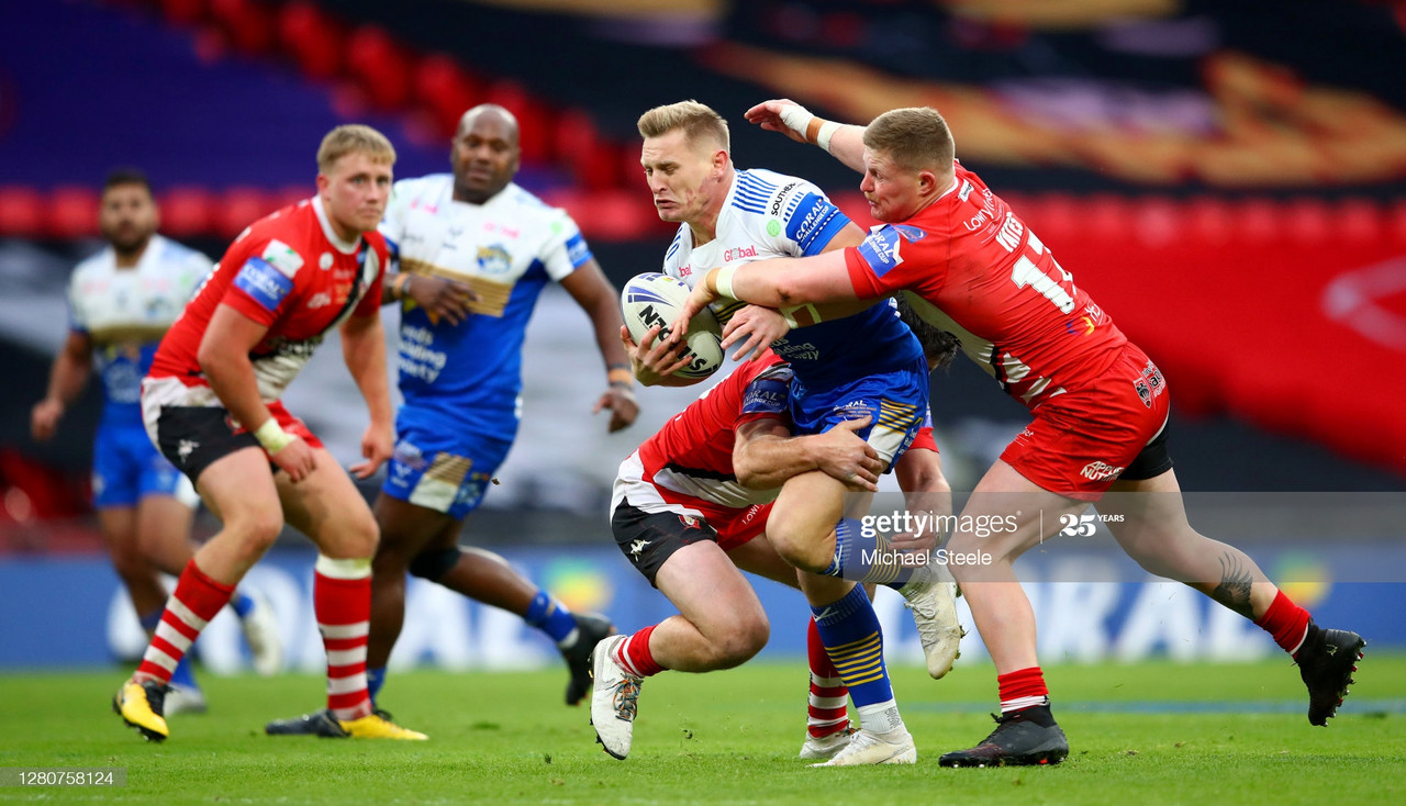 LONDON, ENGLAND - OCTOBER 17: Brad Dwyer of Leeds Rhinos is tackled by Luke Yates of Salford Red Devils during the Coral Challenge Cup Final match between Leeds Rhinos and Salford Red Devils at Wembley Stadium on October 17, 2020 in London, England. Sporting stadiums around the UK remain under strict restrictions due to the Coronavirus Pandemic as Government social distancing laws prohibit fans inside venues resulting in games being played behind closed doors. (Photo by Michael Steele/Getty Images)
