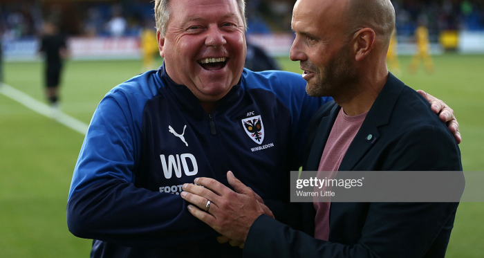 Managers Wally Downes, of AFC Wimbledon and Paul Tisdale of MK Dons share a laugh ahead of kick off in the Carabao Cup First Round match between AFC Wimbledon and Milton Keynes at The Cherry Red Records Stadium on August 13. (Photo by Warren Little/Getty Images)