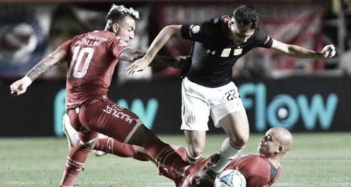 Batallini luchando el balón con Ayala. Foto: Télam.