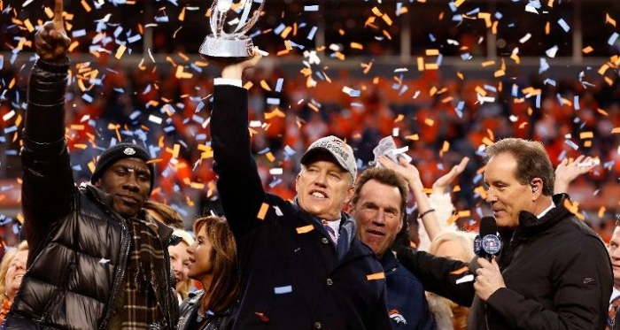 General Manager and Executive Vice President of Football Operation for the Denver Broncos John Elway holds up the Lamar Hunt Trophy with former Bronco Terrell Davis after defeating the New England Patriots in the AFC Championship game at Sports Authority
