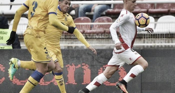 Álex Moreno llevándose un balón frente a dos rivales. Fotografía: Rayo Vallecano S.A.D.
