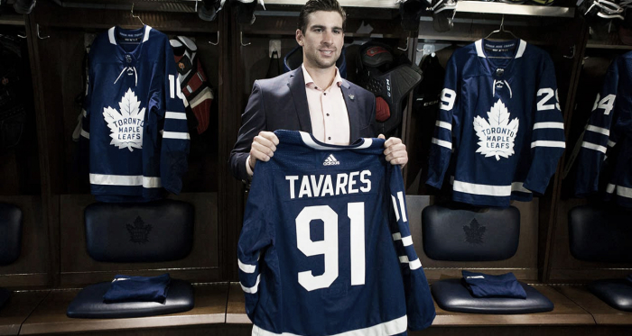 John Tavares holds up a Leafs jersey in the summer after he signed in Toronto. Photo credit - Sportsnet