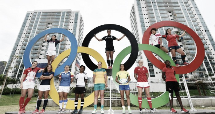 The 12 women's Rugby Sevens captains line-up under the Olympic rings (image via: worldrugby.org)