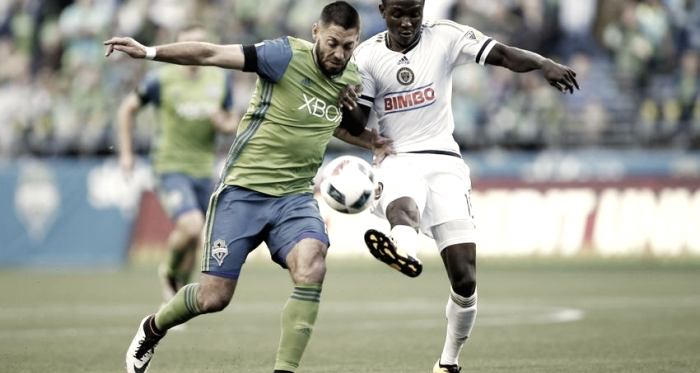 Joshua Yaro jostles with Clint Dempsey during MLS action last season. (Photo credit: USA Today)