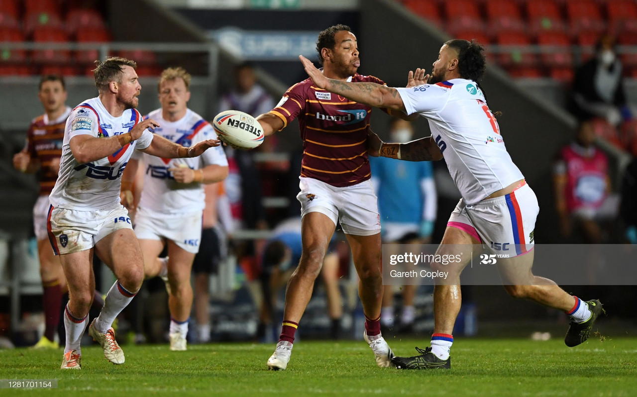 ST HELENS, ENGLAND - OCTOBER 22: Leroy Cudjoe of Huddersfield looks to offload underpressure from David Fifita of Wakefield during the Betfred Super League match between Huddersfield Giants and Wakefield Trinity at Totally Wicked Stadium on October 22, 2020 in St Helens, England.Sporting stadiums around the UK remain under strict restrictions due to the Coronavirus Pandemic as Government social distancing laws prohibit fans inside venues resulting in games being played behind closed doors. (Photo by Gareth Copley/Getty Images)