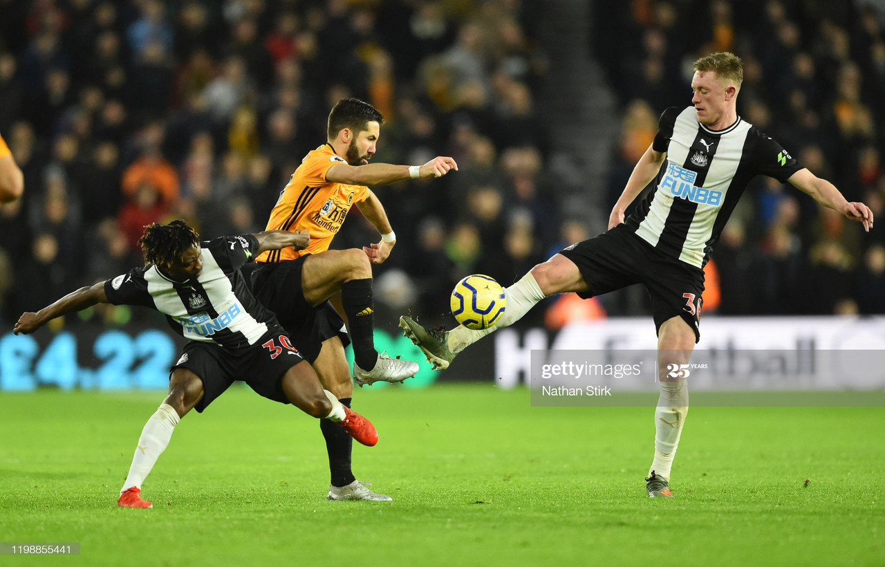 WOLVERHAMPTON, ENGLAND - JANUARY 11: Christian Atsu of Newcastle United battles for possession with Joao Moutinho of Wolverhampton Wanderers during the Premier League match between Wolverhampton Wanderers and Newcastle United at Molineux on January 11, 2020 in Wolverhampton, United Kingdom. (Photo by Nathan Stirk/Getty Images)