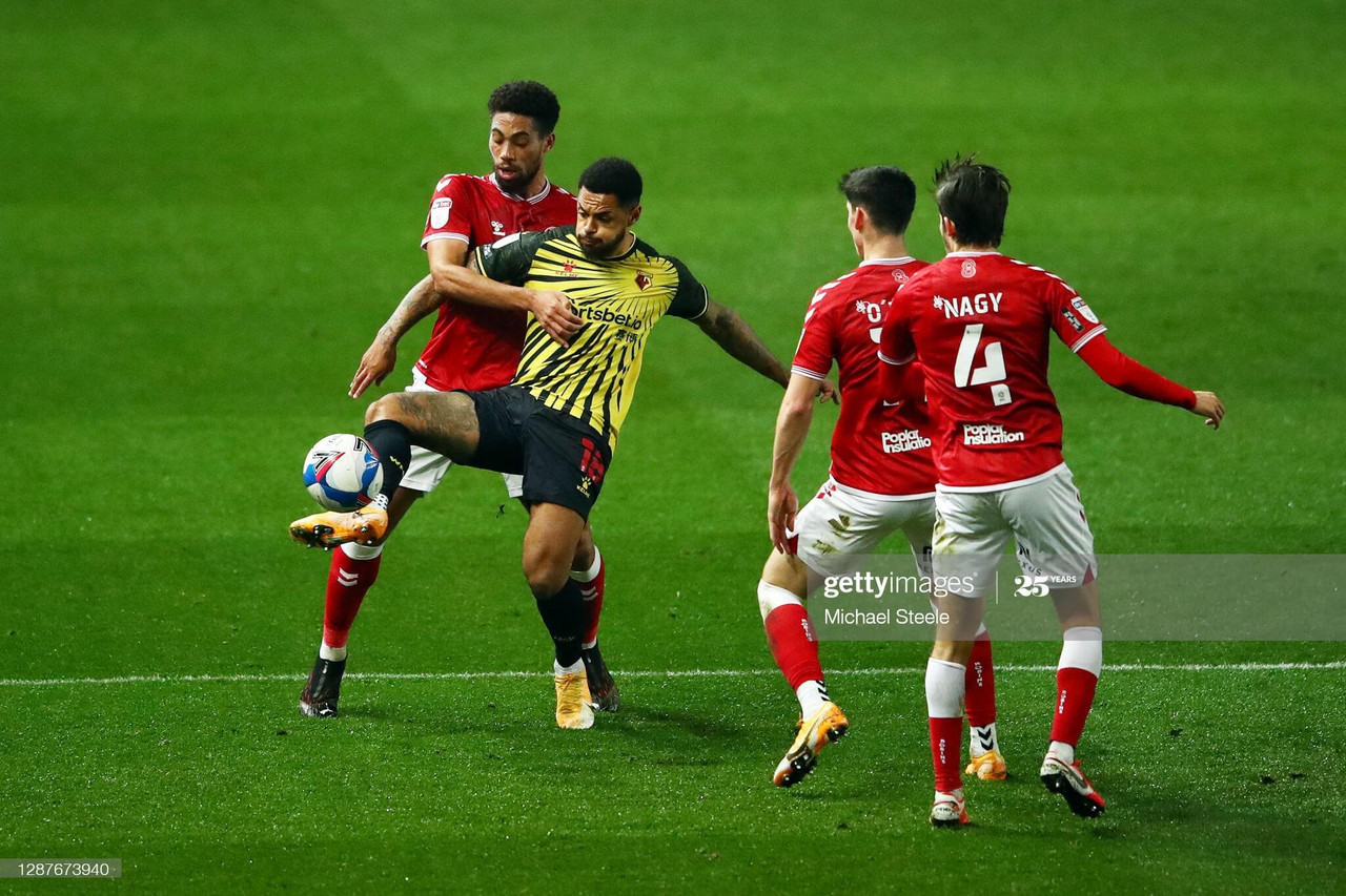 Andre Gray of Watford is challenged by Zak Vyner of Bristol City during the Sky Bet Championship match between Bristol City and Watford at Ashton Gate on November 25, 2020 in Bristol, England. Sporting stadiums around the UK remain under strict restrictions due to the Coronavirus Pandemic as Government social distancing laws prohibit fans inside venues resulting in games being played behind closed doors. (Photo by Michael Steele/Getty Images)