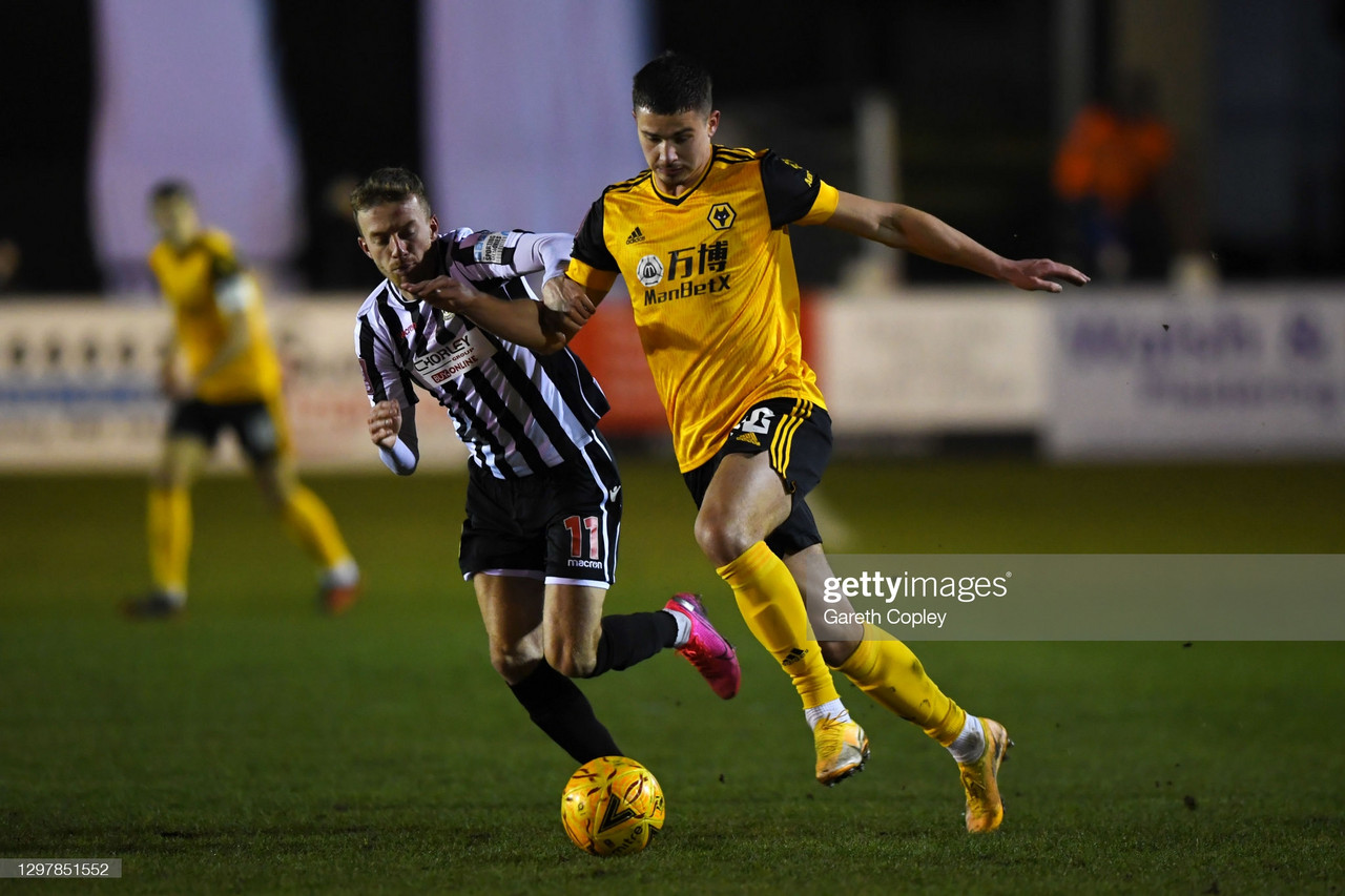 Leander Dendoncker of Wolverhampton Wanderers battles for possession with Elliot Newby of Chorley FC during The Emirates FA Cup Fourth Round match between Chorley and Wolverhampton Wanderers at Victory Park on January 22, 2021 in Chorley, England. Sporting stadiums around the UK remain under strict restrictions due to the Coronavirus Pandemic as Government social distancing laws prohibit fans inside venues resulting in games being played behind closed doors. (Photo by Gareth Copley/Getty Images)
